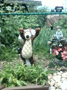 stuffed animal trying to climb over fence